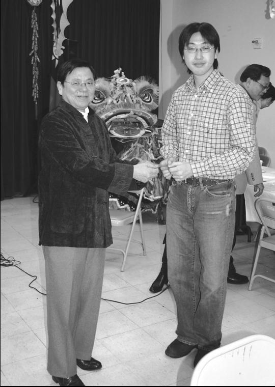 新春團拜董事長陳輝泗發紅包給最年輕的出席校友蔡炅男(84級數學系),同時也祝賀他取得哥大數學博士學位。